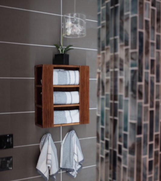 Bamboo towel rack by FATSTICK on porcelain tile wall, reflected in Mirror.